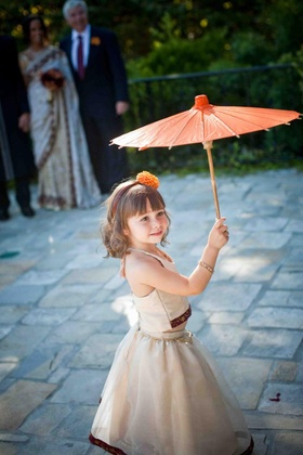 Flower girl in an ivory two-piece outfit with burgundy and gold trim holds an orange parasol