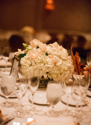 Wedding reception centerpiece of white hydrangea and pale peach roses