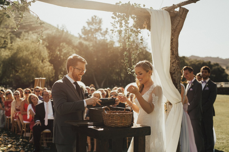 bride and groom participating in wine ceremony at wedding