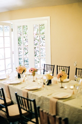 Black chairs and rectangular table with ivory linens