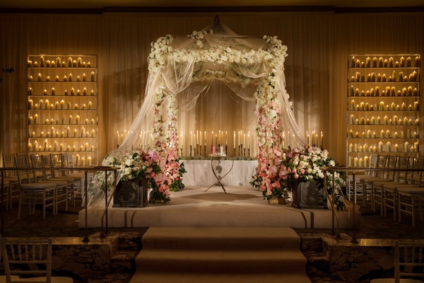 Glamorous indoor garden wedding in new york city inside weddings jewish floral embellished chuppah and candles junglespirit Choice Image