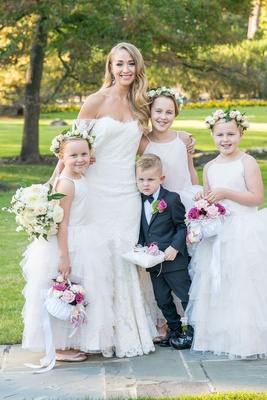Bride in off shoulder anne barge wedding dress with ring bearer pillow and three flower girls