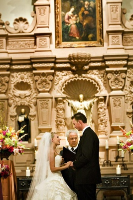 Bride and groom at chapel altar with Catholic priest