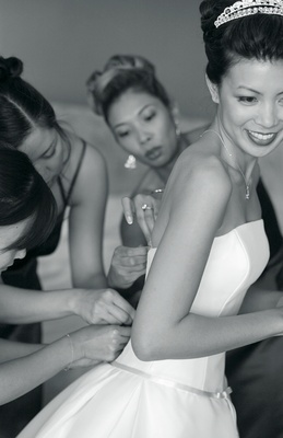 Black and white image of bridesmaids help the bride button her wedding dress