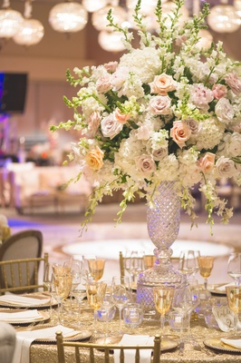 Wedding reception table with cut crystal vase full of white hydrangeas, orchids, pink, light purple