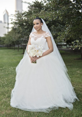 bride in legends romona keveza a-line wedding dress and illusion neckline and cap sleeves
