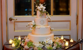 White cake with white flowers and gold monogram