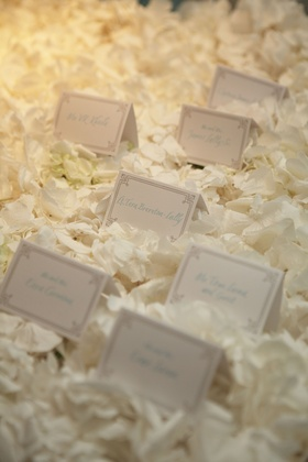 place cards resting on bed of white flower petals