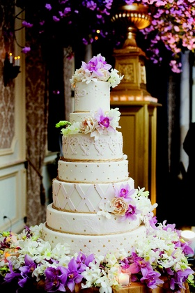 White wedding cake with understated gold accents surrounded by white and purple orchids