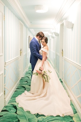 Bride in off the shoulder blush ball gown and groom in navy blue suit in hallway of the colony green