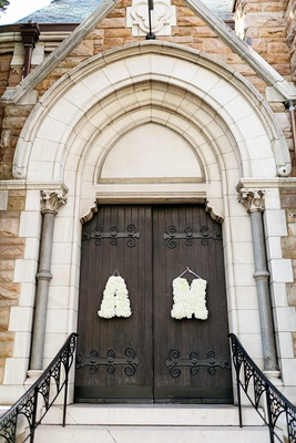 bride and groom's initials in white flowers on church door