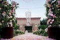Wedding ceremony at Grand Del Mar with flower petal aisle, rose bushes, flower wall and chuppah