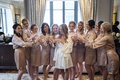 bride in white robe lace trim with bridesmaids champagne robes champagne flutes cheers toast