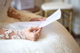 Bride in ball gown illusion sleeves pearl embellishments reading handwritten note