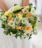 Wedding bouquet with white flowers, light orange roses, yellow blooms and greenery colorful