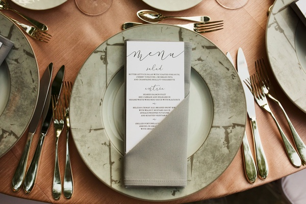 Wedding menu with modern calligraphy salad entree choices in grey napkin on wood table
