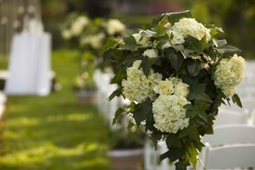Outdoor wedding ceremony with an arrangement of white flowers and ivy