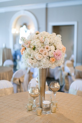 Wedding reception table with light orange roses, white roses, hydrangeas, pink dahlias in gold vase