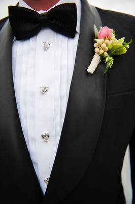 Groom in tuxedo with silver buttons and black bow tie textured boutonniere pink flower