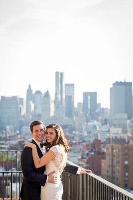 Wedding couple in tuxedo and gown from Mark Ingram Atelier on rooftop balcony with view of city