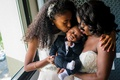 bride in strapless wedding dress and flower girl with little ring bearer baby in tuxedo sleeping