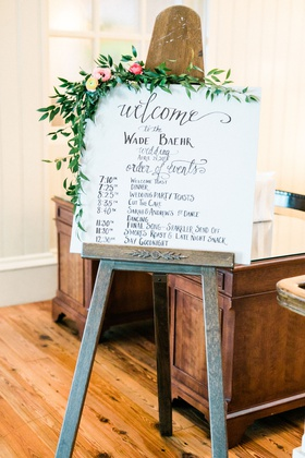 wedding reception easel with welcome sign and itinerary greenery pink flowers wood