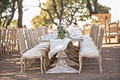 Wedding reception outside long wood pedestal tables with wood chairs upholstered linen runner