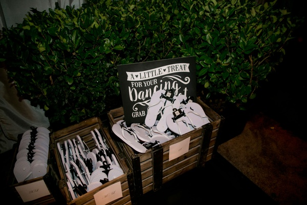 Alexis Cozombolidis and Hunter Pence wedding reception favors white and black flip flops with sign