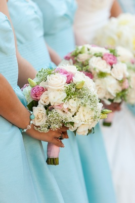 Bridesmaids holding white and pink flowers at ceremony