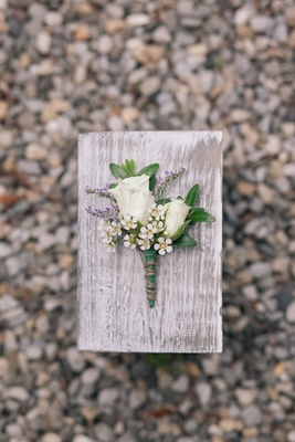 Rose and purple boutonniere on wood plank