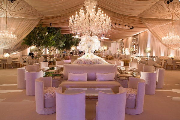 Tent wedding reception with plush furniture and chandeliers