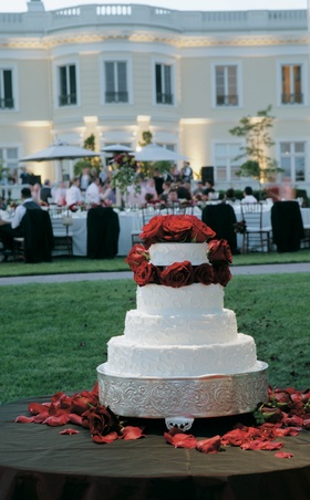 White wedding cake embellished with red roses