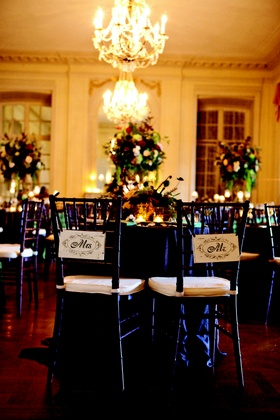 Bride and groom wedding reception seating with wooden signage