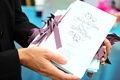White ceremony booklets with purple ribbons