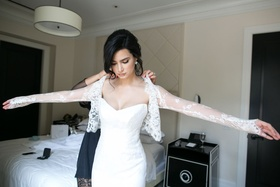 Bride getting help in bridal suite strapless wedding dress with long sleeve lace bolero illusion