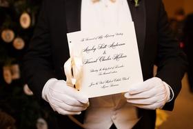 Man in white gloves holding formal ceremony program white stationery and black calligraphy ribbon