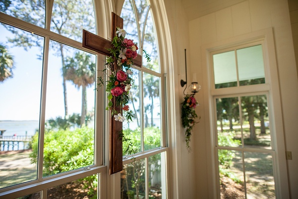 Wood cross on arch window of chapel Montage Palmetto Bluff yellow and pink flowers with greenery