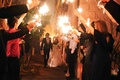 Bride and groom walk through tunnel of sparklers