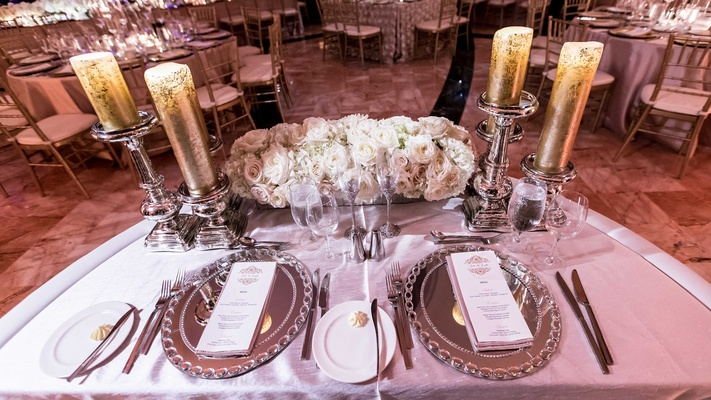 Wedding reception sweetheart table with mirror chargers, gold pillar candles on mercury glass stands