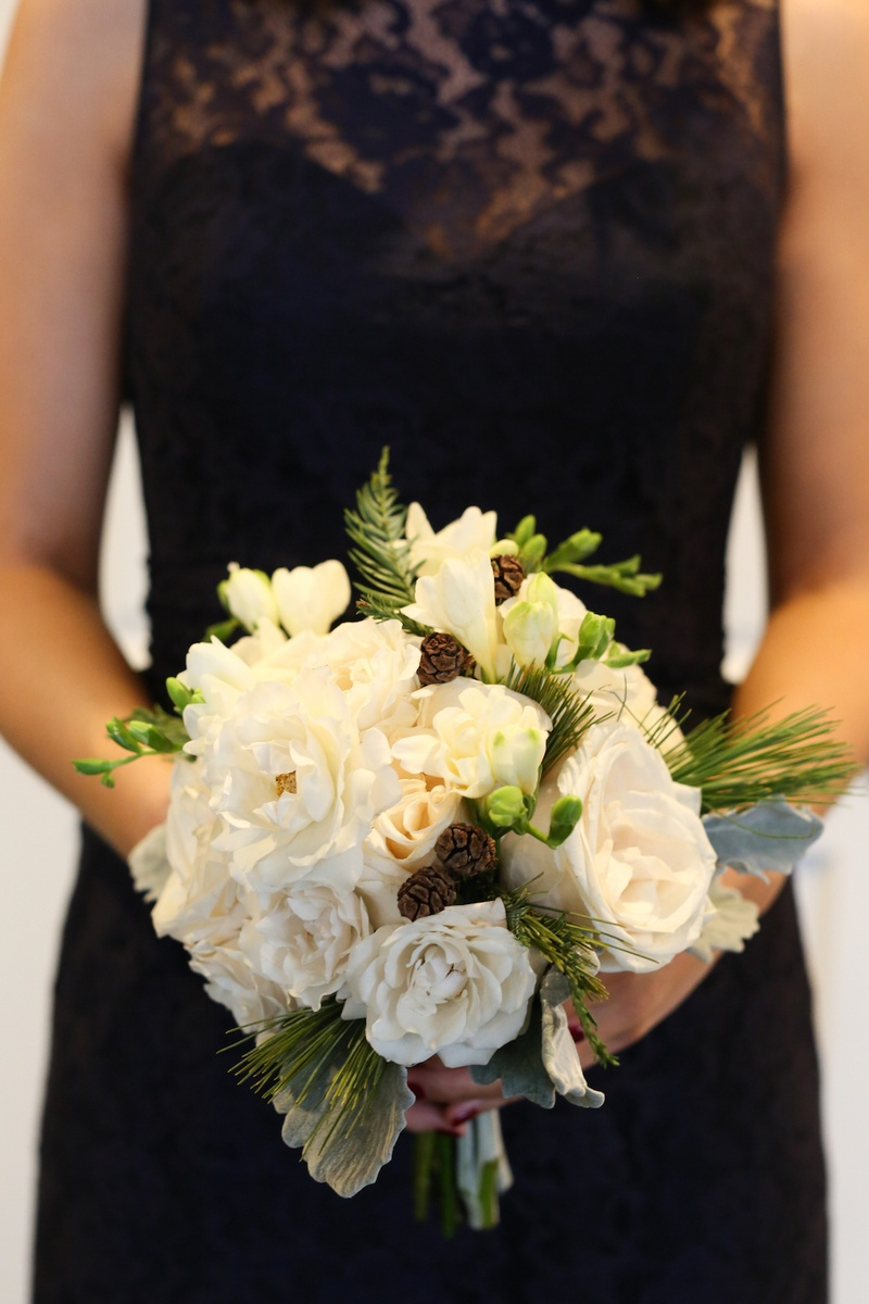 Winter wedding bouquet with white flowers, pinecones, and evergreen foliage