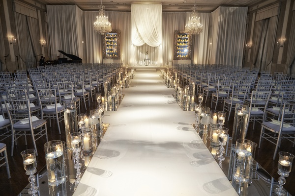 White aisle lined with candles leading to chuppah