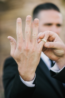 Best man in black tuxedo shows the groom's yellow gold wedding ring and bride's diamond wedding ring
