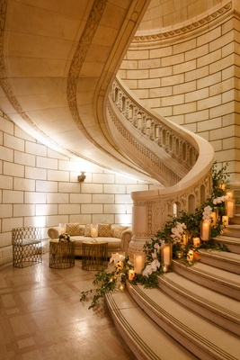 wedding reception grand staircase decorated with greenery candles white flowers chesterfield sofa