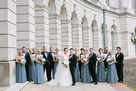 bride and groom with large wedding party bridesmaids in blue floor length bridesmaid dresses