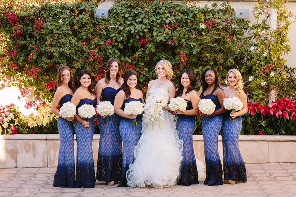 Bride in Demetrios, bridesmaids in betsey and adam dresses in shades of blue