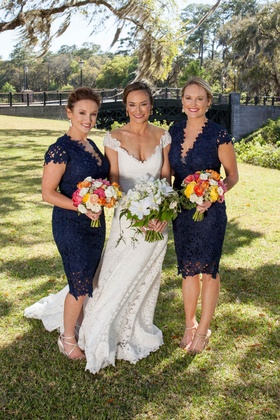 Bride in v neck lace Romona Keveza wedding dress and short blue lace plunging short sleeve dresses