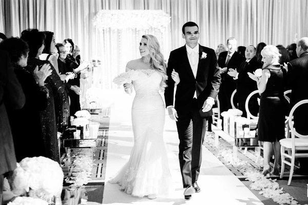 black and white wedding photo ceremony recessional bride in formfitting illusion gown groom in white