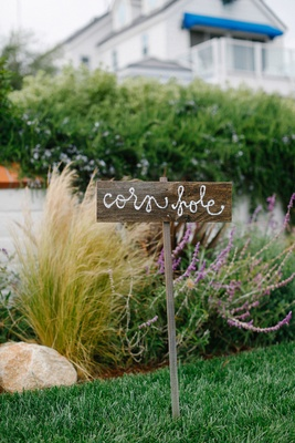 Waterfront wedding lawn with cornhole written on a weathered wood sign