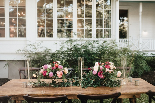 wood wedding reception table outdoor greenery pink white flowers taper candles