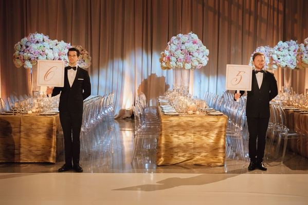 Wedding reception table number idea have male models in tuxedos hold table numbers for guests